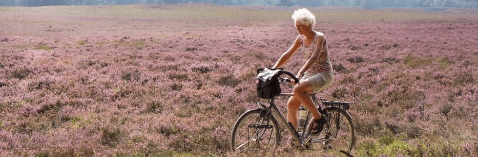 senior riding bike in field
