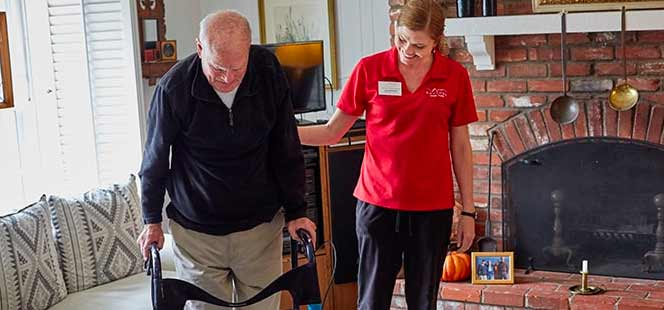 Caregiver offering in room care to senior man with walker.