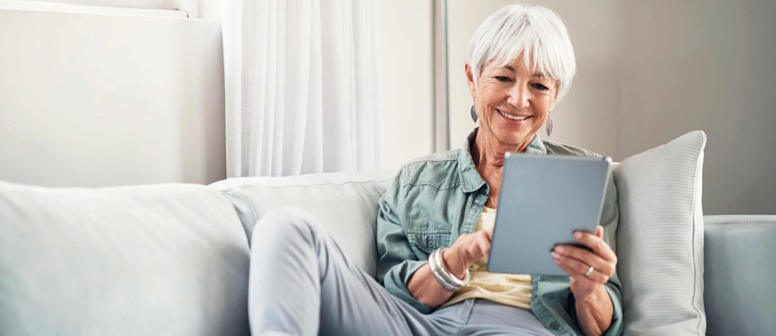 Senior woman using tablet while sitting on couch